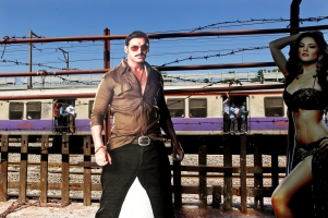 "A train moves past a cutout of Bollywood actors John Abraham and Sunny Leone displayed outside a cinema hall in Mumbai, India, Friday, May 3, 2013. Four top Indian filmmakers have come together to make ""Bombay Talkies,"" a short-film collection that hits theaters Friday to celebrate 100 years of Indian cinema. India's first full-length feature film ""Raja Harishchandra,"" or ""King Harishchandra,"" was released in 1913. Since then Indian cinema has become the largest producer of films in the world. India produced nearly 1,500 films last year, according to accounting firm KPMG. (AP Photo/Rajanish Kakade)"